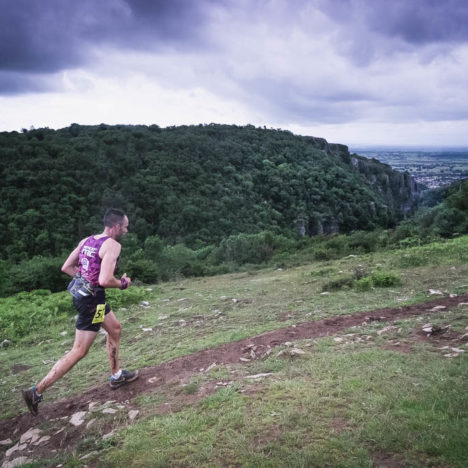 A runner at the Top of Cheddar Gorge with dark moody clouds