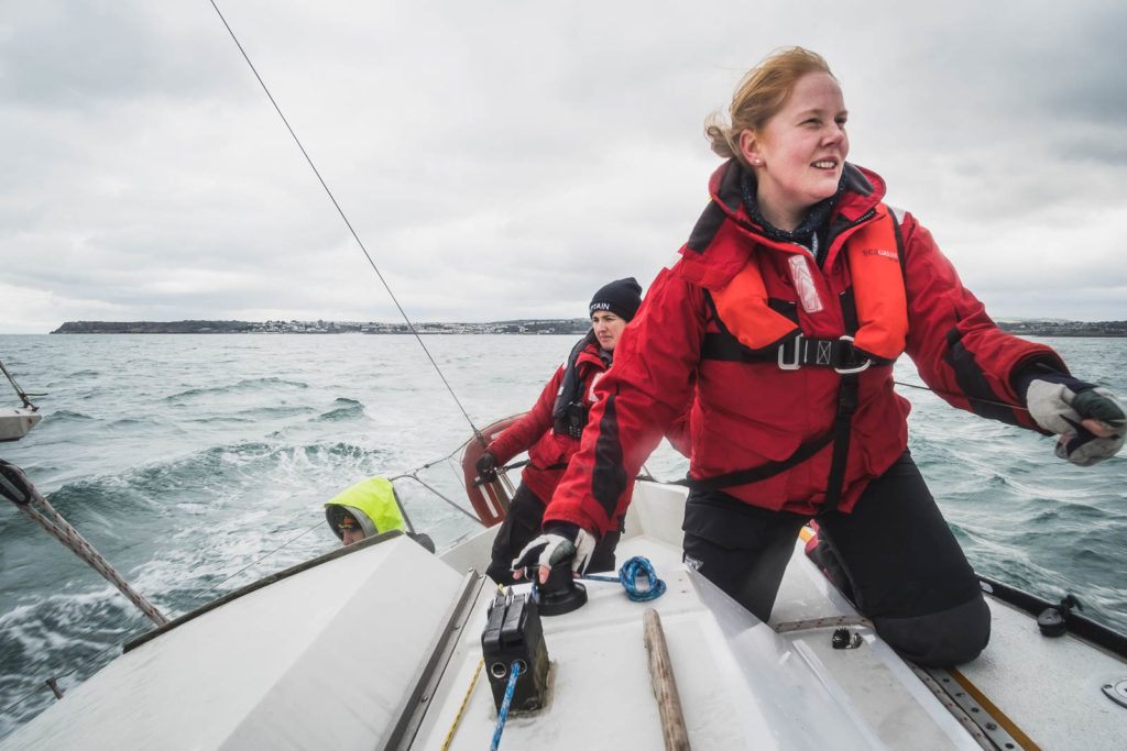 A woman sailing in choppy waters with a red lifejacket and oilies