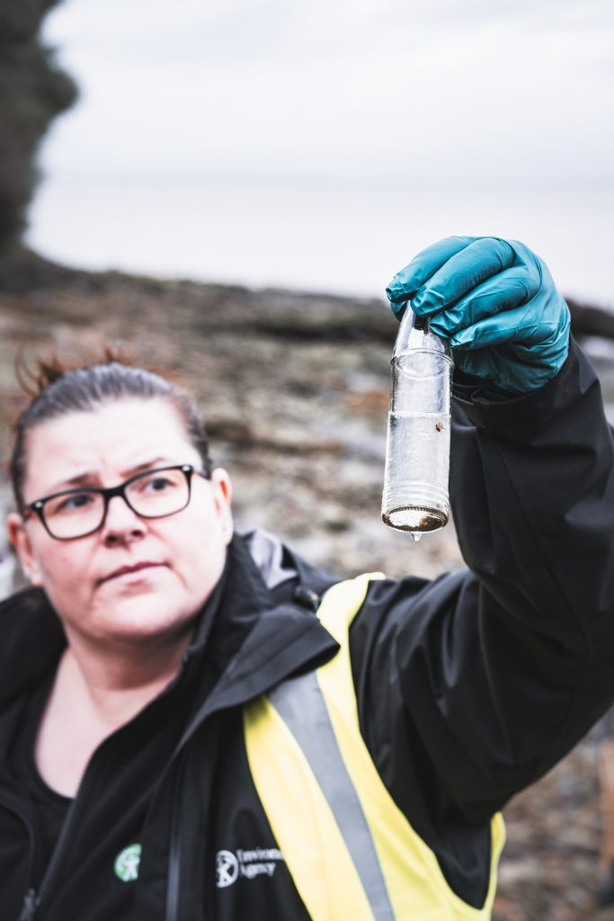 The environment agency litter picker looking at a small shrimp creature stuck in pulltion