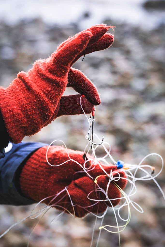 Example of fishing gear washed up on a beach being held with some red gloves